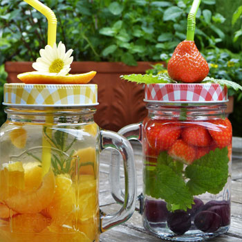 Wasser trinken mit Erdbeeren, Trauben, Orange und Minze