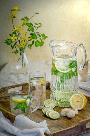 Wasser trinken mit Zitronen, Limetten und Ingwer